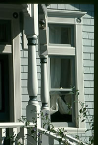 Porch Posts installed on a front porch with wood railing and balusters.